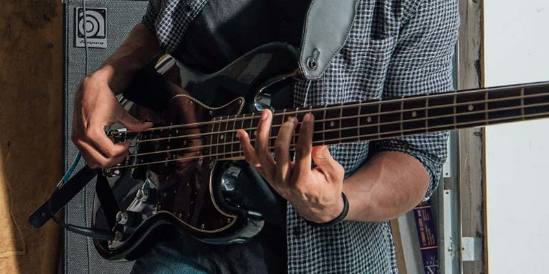 A person playing a bass guitar with a pick