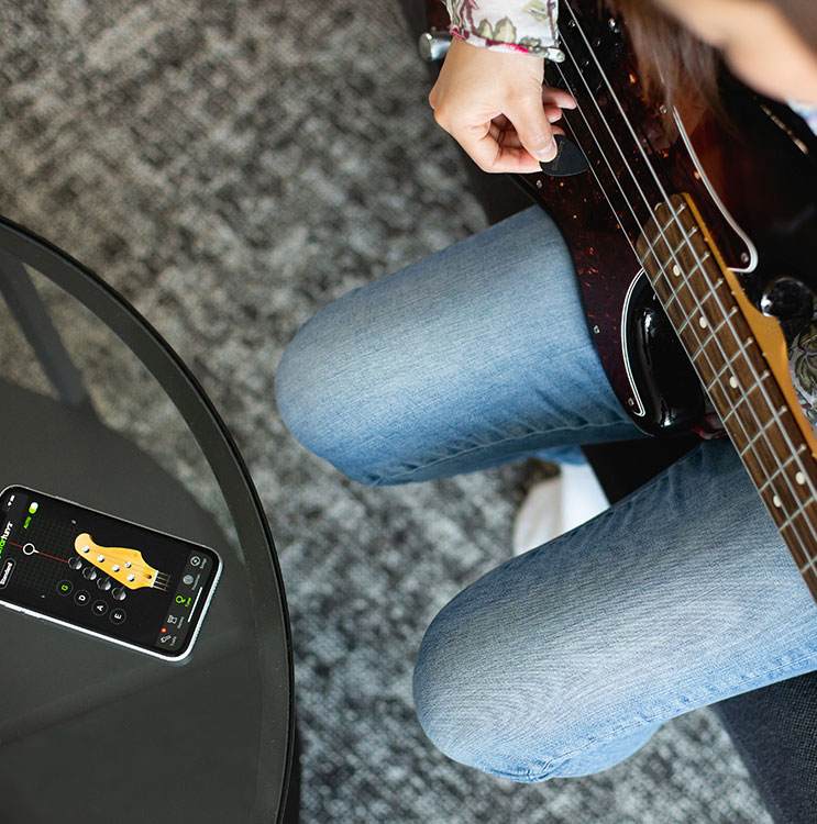 A Lady tuning bass guitar with app