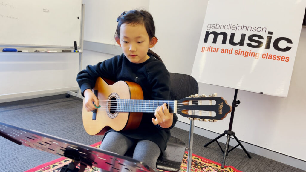 Gabrielle Johnson Music School student Raleigh on acoustic guitar